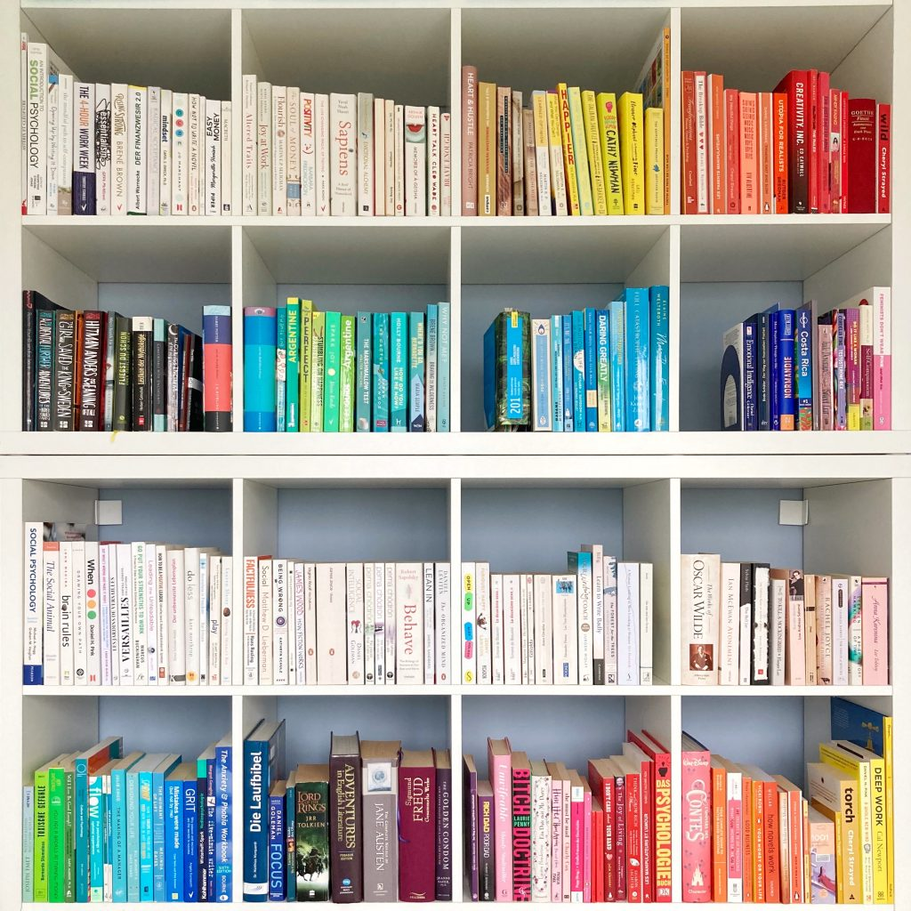 a picture of a book case with books sorted by color that i want to talk about on my book blog