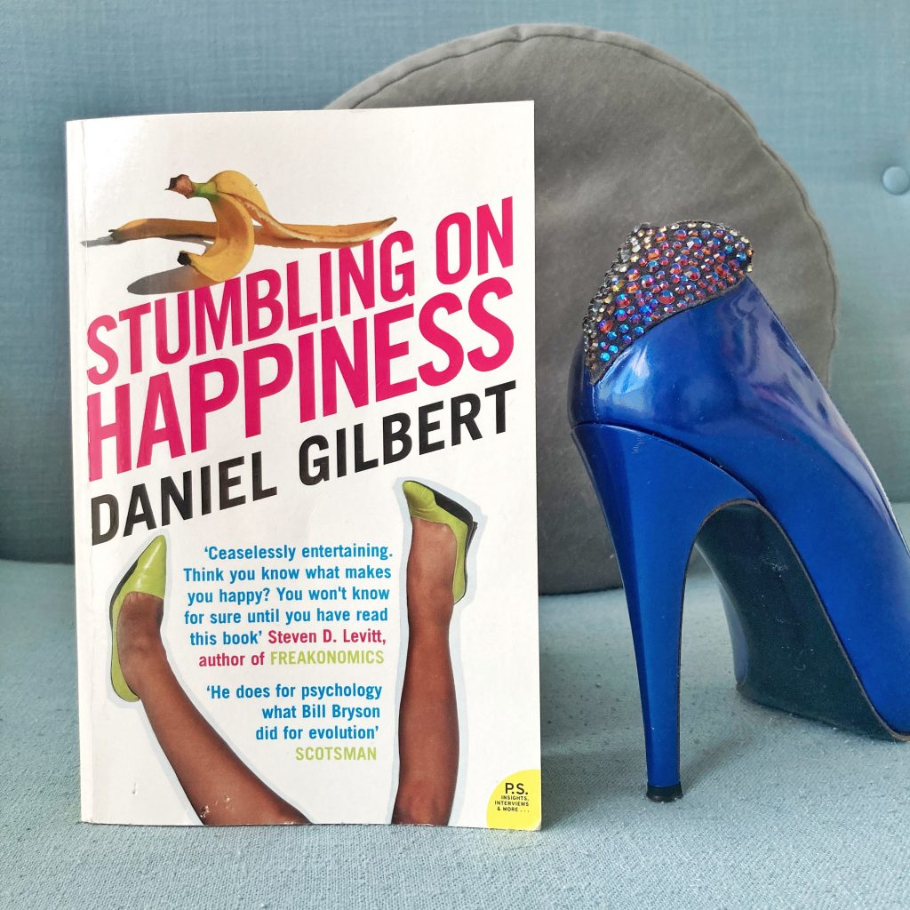 picture of the cover of stumbling on happiness next to a blue shoe with rhinestones