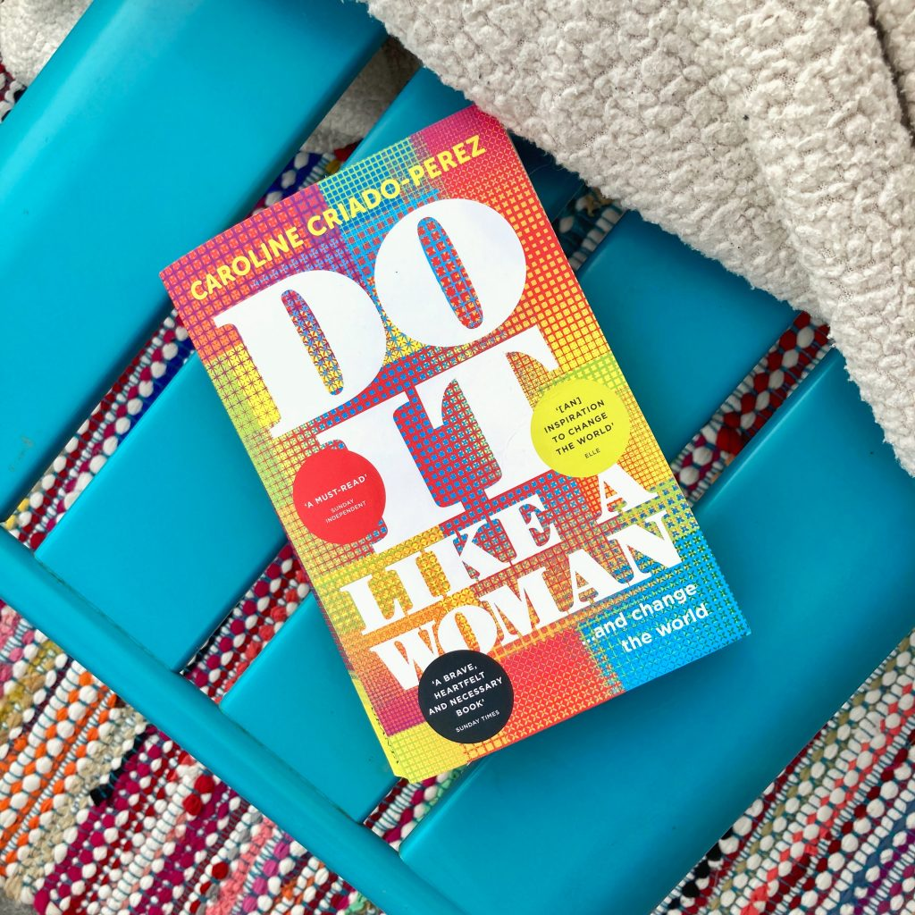 the cover of 'do it like a woman' on a chair with a blanket