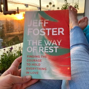 my hand holding up the book the way of rest by jeff foster