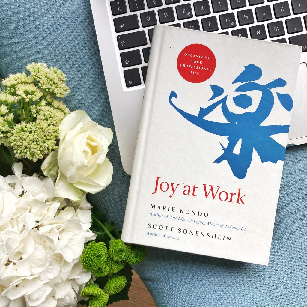 the book joy at work positioned on a labtop next to flowers